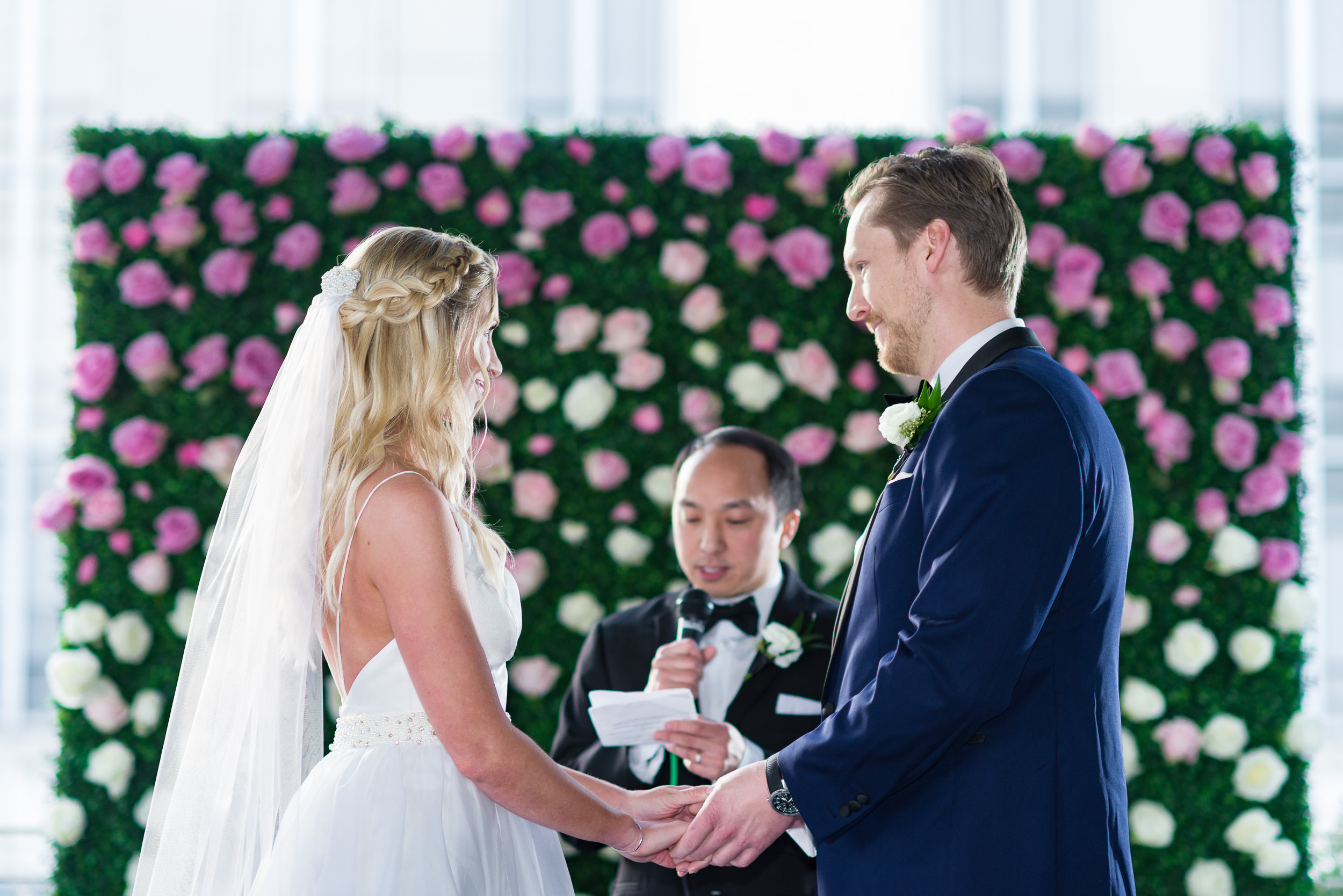 Austin-wedding-photographers-ceremony-brazos-hall-downtown-flower-backdrop-pink-roses